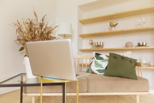 Laptop dichtbij bank in woonkamer