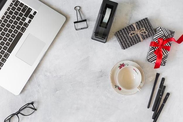 Laptop dichtbij huidige dozen, kop op schotel en kantoorbehoeften