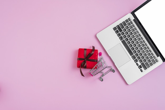 Laptop dichtbij uiterst klein boodschappenwagentje en cadeau