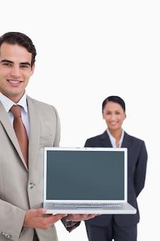 Laptop die door glimlachende verkoper met collega achter hem wordt voorgesteld