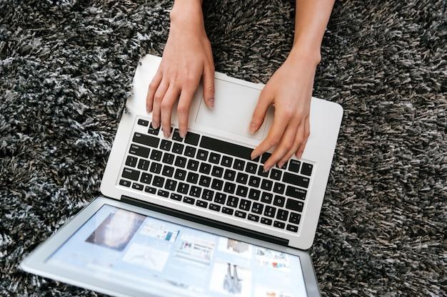 Laptop die door vrouwenhanden wordt gebruikt op het tapijt