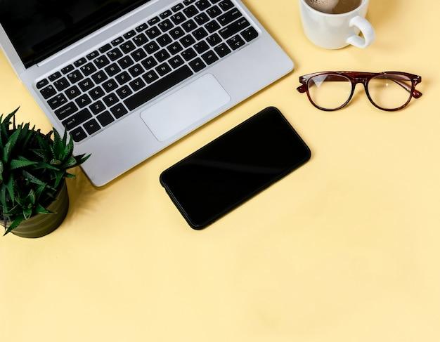 Laptop die op een gele lijst van bedrijfs werkende plaats met kopkoffie wordt geplaatst, lege werkruimte