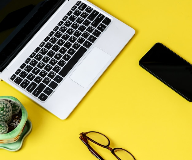 Laptop die op een gele lijst van bedrijfs werkende plaats met kopkoffie wordt geplaatst