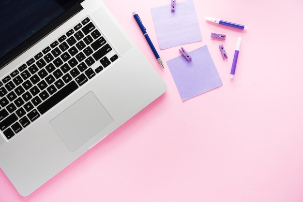 Laptop en benodigdheden met roze achtergrond