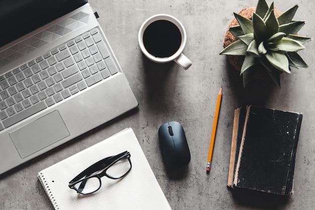 Laptop en boek, koffie op grijze achtergrond, bovenaanzicht van bureau op gestructureerde grijze achtergrond