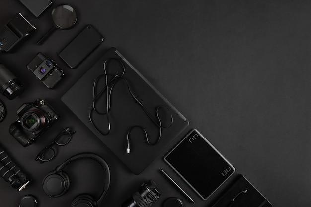 Laptop en cameramateriaal schikte op zwarte abstracte bureauachtergrond met lege ruimte. fotograaf werkplekconcept.
