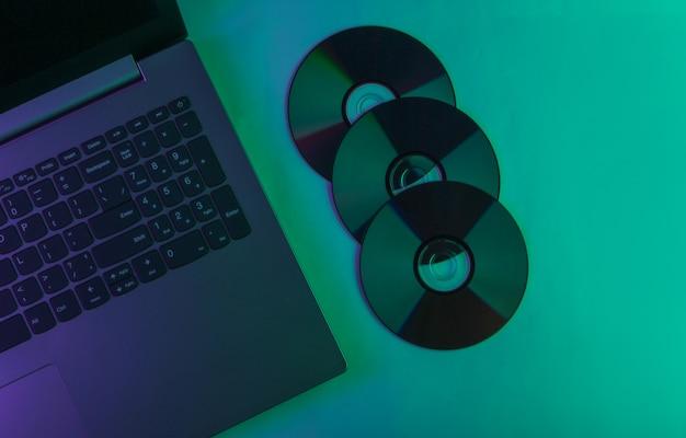 Laptop en cd-schijven met neon groen en paars licht