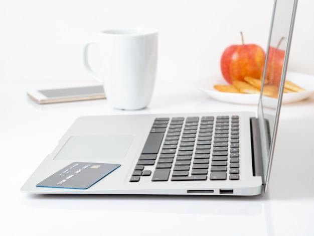 Laptop en creditcard, betalen voor aankopen per creditcard, online winkelen, witte achtergrond