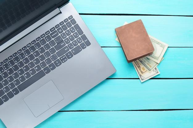Laptop en een tas met geld op een turquoise houten tafel. het concept van online werken op internet, freelancen. bovenaanzicht