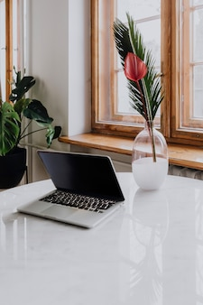 Laptop en een vaas op een marmeren tafel