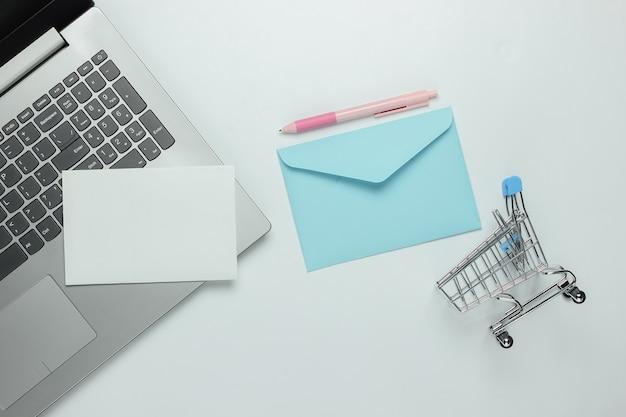 Laptop en envelop met brief, winkelwagentje op witte achtergrond. valentijnsdag. bovenaanzicht
