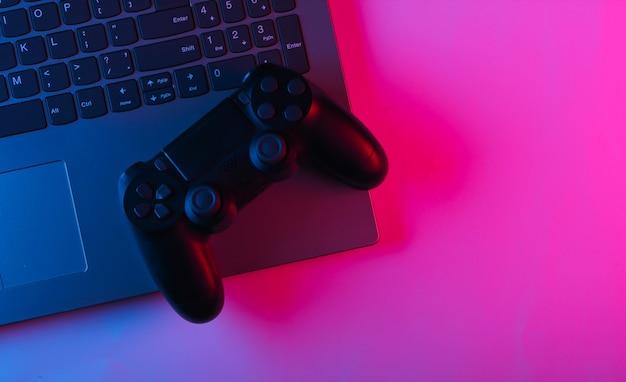 Laptop en gamepads met blauw roze neon levendig licht.