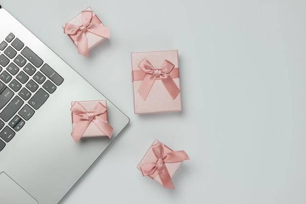 Laptop en geschenkdozen met bogen op witte achtergrond. samenstelling voor kerst, verjaardag of bruiloft. kopieer ruimte. bovenaanzicht