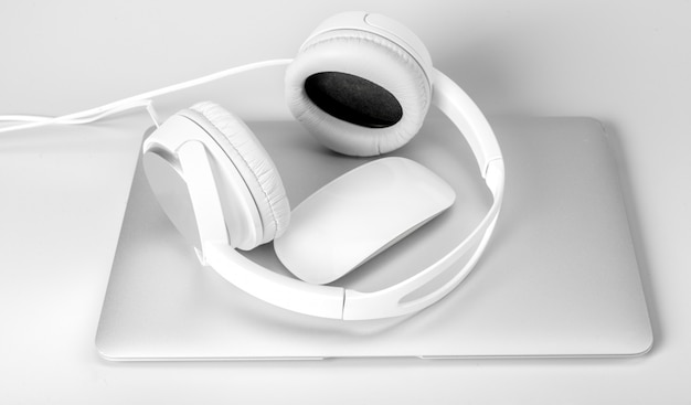 Laptop en hoofdtelefoon op wit wordt geïsoleerd dat