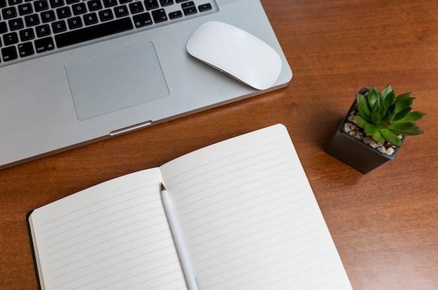 Laptop en kladblok met pen op een houten tafel thuis. werken op afstand in quarantaine. zelfisolatieregime tijdens de pandemie van het coronavirus. uitzicht van boven. ruimte voor tekst.