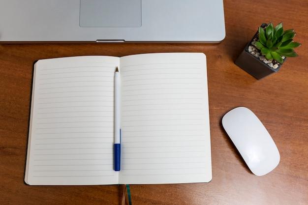 Laptop en kladblok met pen op een houten tafel thuis. werken op afstand in quarantaine. zelfisolatieregime tijdens de pandemie van het coronavirus. uitzicht van boven.