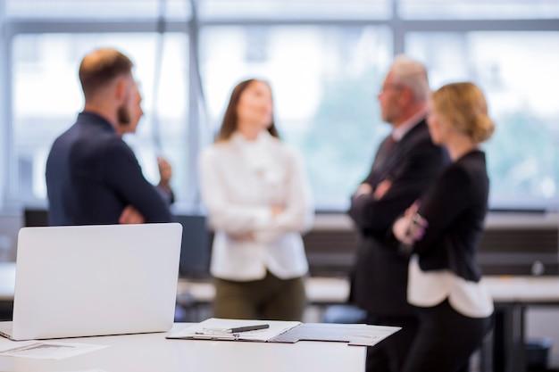 Laptop en klembord met pen op tafel met intreepupil zakenmensen op achtergrond