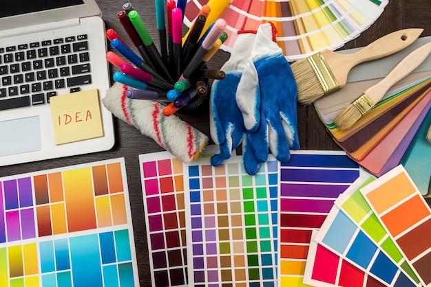 Laptop en kleurenpalet met penseel en handschoenen voor uw designhuis op kantoor