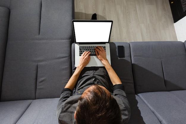 Laptop en koffiekop in de handen die van het meisje op een houten vloer zitten