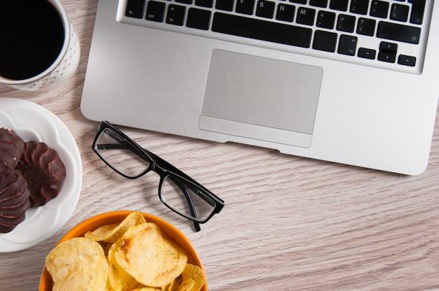 Laptop en kom chips op houten lijst. slechte gewoonten concept