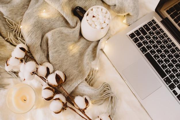 Laptop en kopje cacao met marshmallows, sjaal, katoenen bloemen, fonkelende lichten, kaars op wit bed. werk thuis concept. herfst, herfst, winter concept. plat lag, bovenaanzicht, kopieer ruimte.