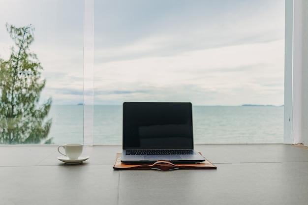 Laptop en kopje koffie op hotelbalkon met uitzicht op zee vanuit hotel