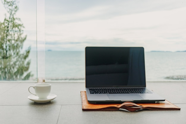Laptop en kopje koffie op hotelbalkon met uitzicht op zee werken vanuit hotel