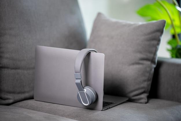 Laptop en koptelefoon tempo op de bank thuis