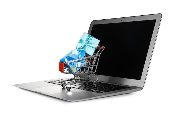Laptop en mini-markt trolley met geschenken, geïsoleerd op wit. internet winkelconcept