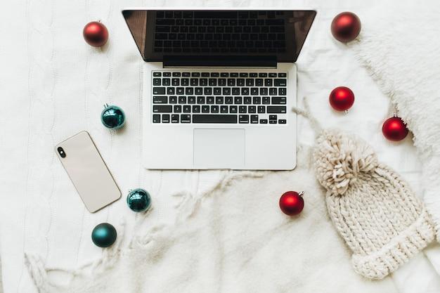 Laptop en mobiel liggend op het witte bed met witte deken versierd met rode en blauwe kerstballen en winter gebreide muts