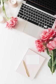 Laptop en mooie roze pioenrozen tulp bloemen, blanco vel papier kaart, kaarsen op wit