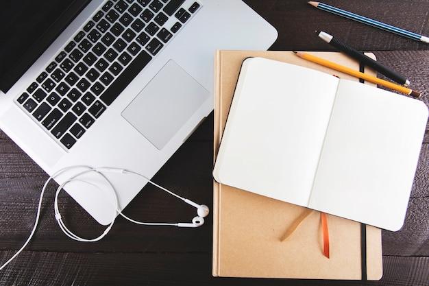 Laptop en oortelefoons dichtbij blocnotes en potloden