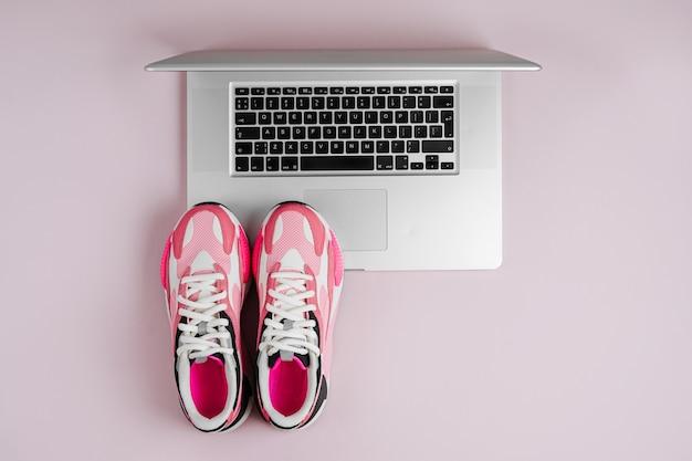 Laptop en sneakers op een roze achtergrond. online fitnessprogramma. thuis workout