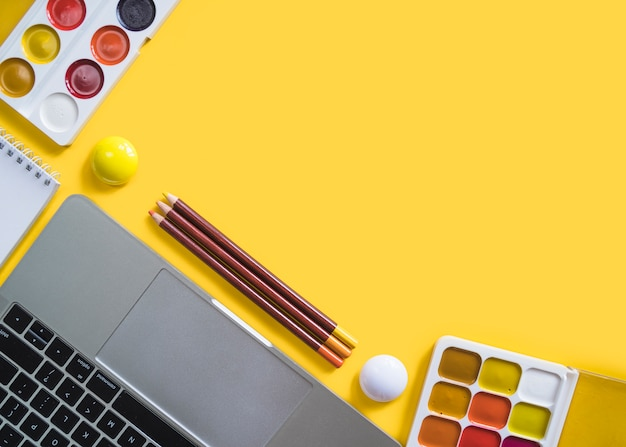 Laptop en verven op geel oppervlak
