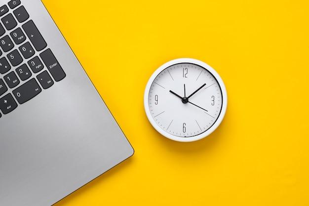 Laptop en wekker op gele achtergrond. de tijd loopt weg. het concept van urgente deadlines op het werk en verplichtingen. bovenaanzicht. plat leggen