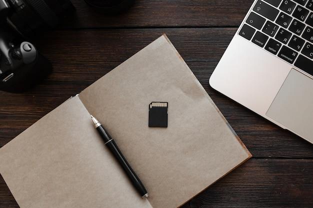 Laptop, flash drive, ambachtelijke notebook, pen en camera op een donkere houten tafel