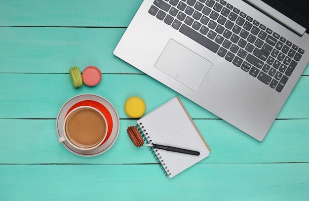 Laptop, gekleurde bitterkoekjes cookies, kopje koffie, notebook met een pen op een blauwe houten tafel. bovenaanzicht. plat liggen