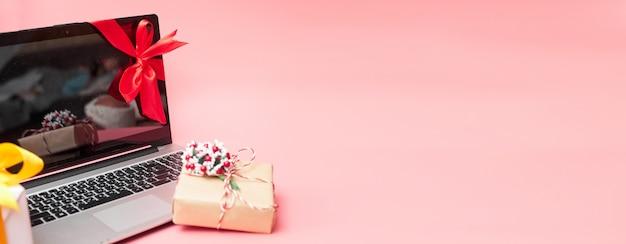 Laptop in een rood lint met geschenken, op een roze achtergrond, banner, kopieer ruimte