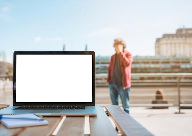 Laptop; kladblok en pen op houten tafel met man die op de achtergrond