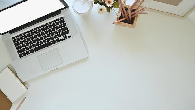 Laptop, koffie, notitieboekjedocument en potlood van het bureaubovenkant met fotokader en bloem op exemplaarruimte.