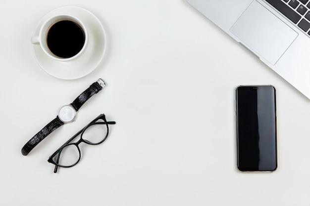 Laptop, koffie, polshorloge, smartphone, bril op witte achtergrond
