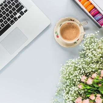 Laptop; koffiekop; bitterkoekjes en bos bloemen op witte achtergrond