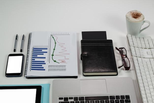 Laptop, koffiemok, smartphone, zakelijke grafiek en bureaubladen