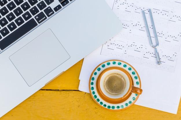 Laptop, kopje koffie en muzieknoten