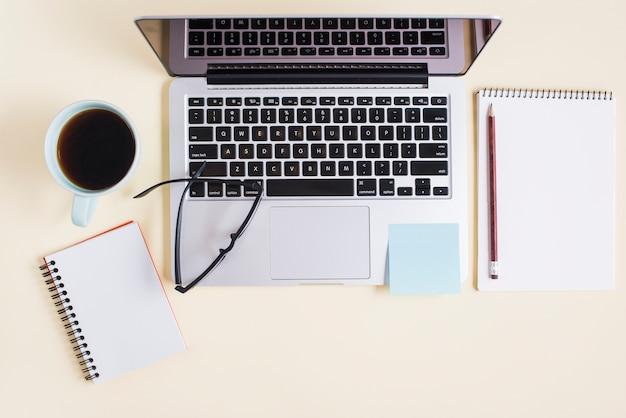 Laptop; kopje thee; spiraal notitieblok; brillen en laptop op beige achtergrond