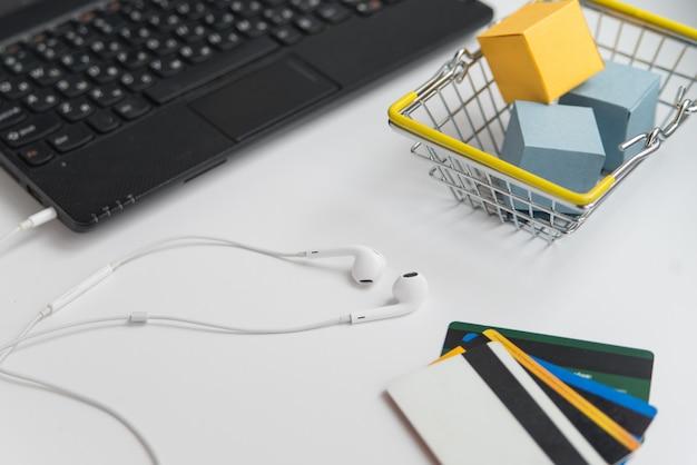 Laptop, koptelefoon, winkelwagen en creditcards. online winkelen en levering conceptie horizontale foto