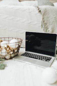 Laptop liggend op de witte deken versierd met kerstboomtakken en feestelijke mand met witte en gouden ballen