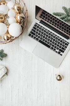 Laptop liggend op houten tafel versierd met kerstboomtakken, feestelijke mand met witte en gouden ballen