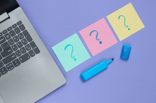 Laptop, memoblaadjes papier met getrokken vraagtekens en viltstift op paarse achtergrond.
