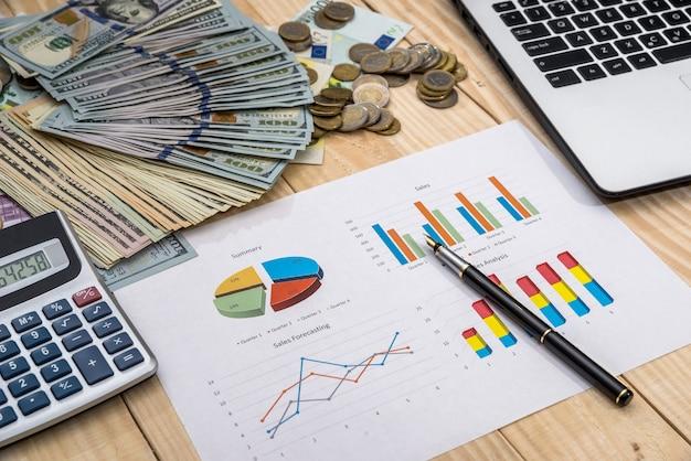 Laptop met bedrijfsdiagram, dollar en rekenmachine